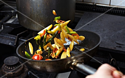 Vegetables being sauteed in a pan on a hob