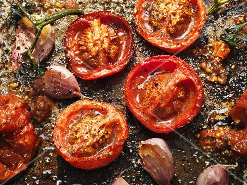 Roasted garlic and tomatoes on a baking tray