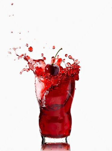 A splashing glass of cherry juice
