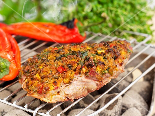 A lamb steak with a herb crust and red peppers on a barbecue