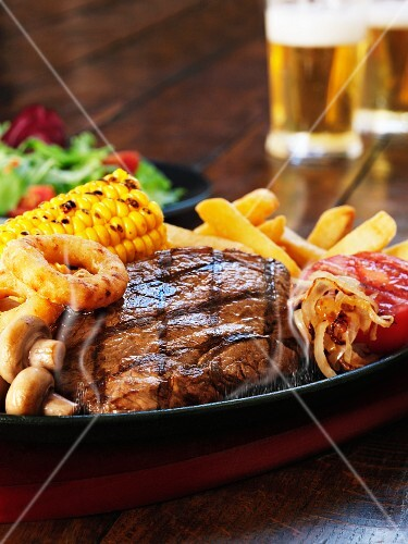 Grilled beefsteak with corn on the cob, mushrooms, onion rings and chips