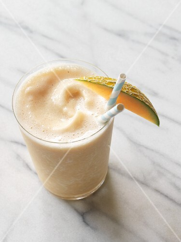 A melon and peach smoothie made with soy milk in a glass garnished with a melon wedge