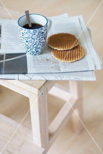 A cup of coffee and syrup waffles on a newspaper