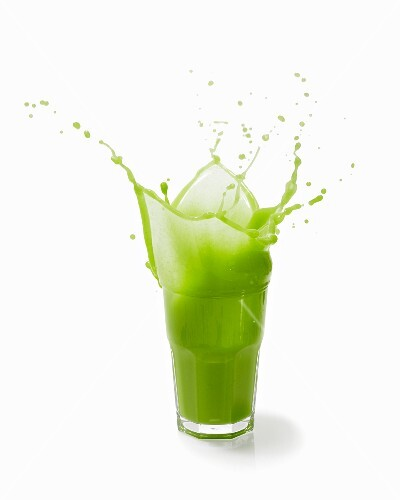 A splashing vegetable smoothie against a white background