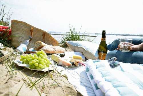 A picnic on a beach with grapes, cheese, bread and wine