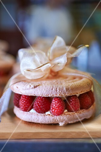 A macaroon cake with raspberries tied with a ribbon