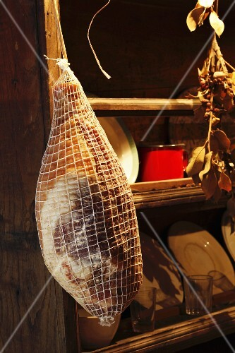 Prosciutto hanging in a kitchen cupboard