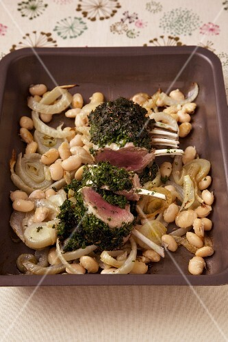 Saddle of lamb in a herb coating on a bean medley