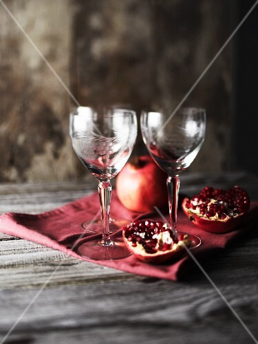 A pomegranate and wine glasses