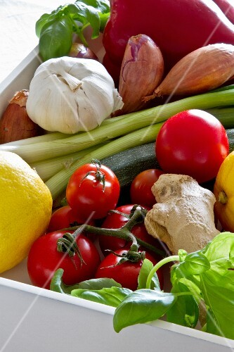 An arrangement of various types of vegetables in a white wooden crate