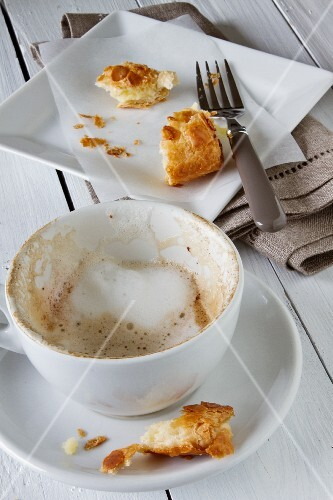 Remains of milk foam in a cappuccino cup and the last pieces of an apple turnover