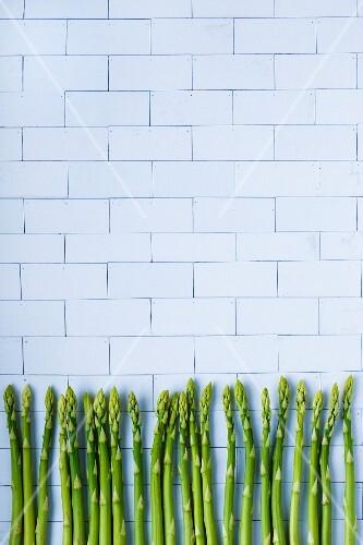 Green asparagus spears against a wall