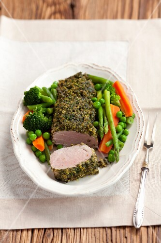 Pork loin with a parsley coating served with spring vegetables