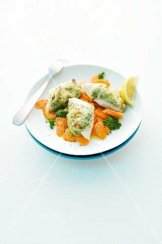 Fish fillet topped with potato served with a carrot medley