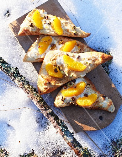 Ricotta pizza with oranges and chopped pistachio nuts