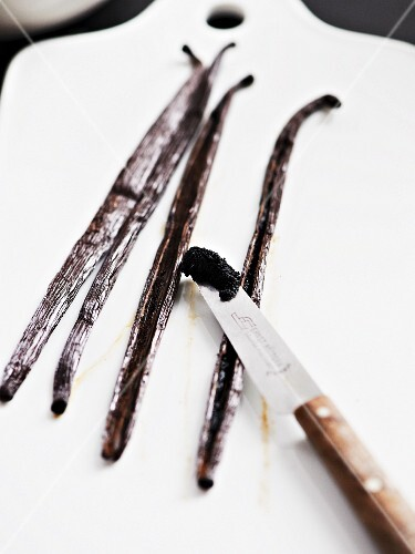 Vanilla pods and scrapped out seeds on a knife