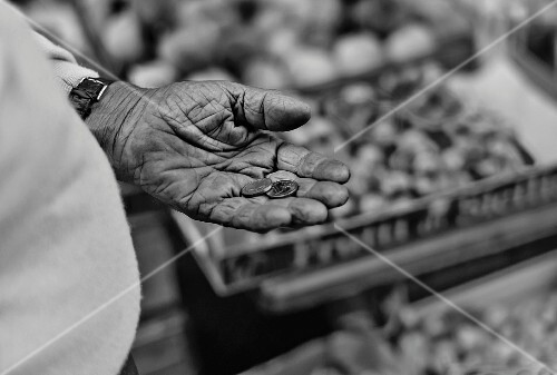 A market stand and a man holding money in his hand