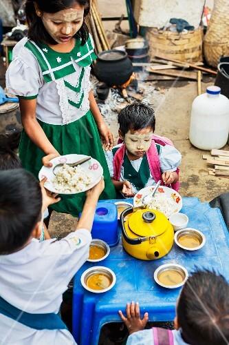 School children eating breakfast at a market in Myanmar