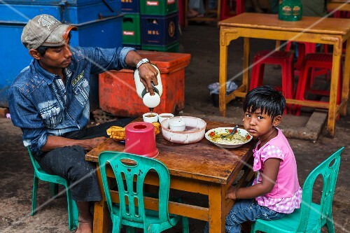 A father and daughter eating breakfast at a market in Myanmar