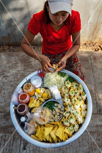 A woman selling grilled tofu at a market in Myanmar