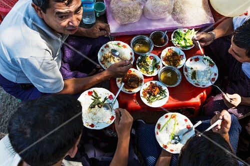 Burmese people eating lunch at a street bar at a market in Myanmar