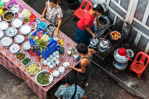 Burmese people selling street food at a market in Myanmar