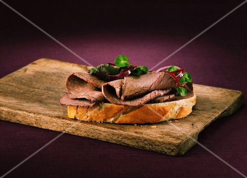 A slice of white bread topped with roast beef on a wooden board