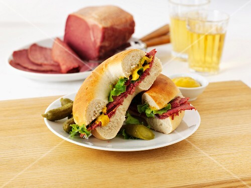A pastrami, salad and mustard bagel served with gherkins
