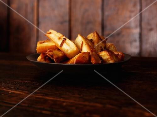 Honey-roasted parsnips on a black plate
