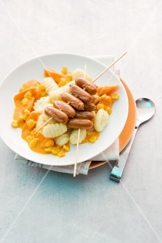 Gnocchi with carrot sauce and a sausage skewer
