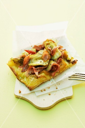 A pizza topped with artichokes and ham