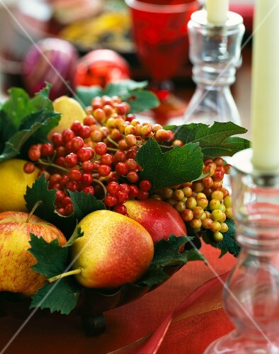 An arrangement with a large fruit bowl and a glass candle holder