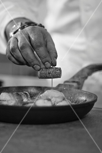 A chef preparing a fish dish (black-and-white image)