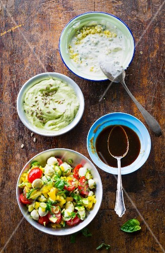A colourful salad, a chive an dlemon dip, teriyaki sauce and avocado cream