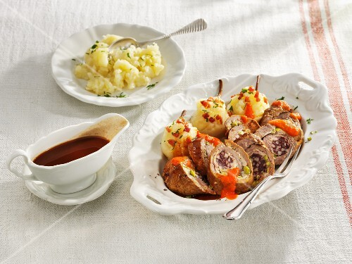 Roast beef roulade filled with blood sausage on a bed of pear potatoes