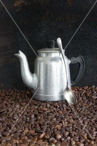 An aluminium coffee jug and a spoon on coffee beans