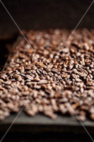 Coffee beans spread over a wooden table