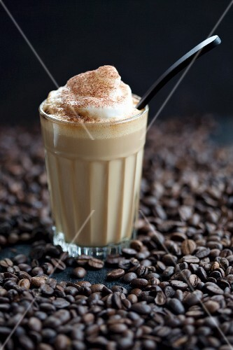 A glass of latte macchiato on coffee beans