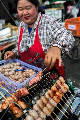 A woman grilling sausages (Bangkok, Thailand)