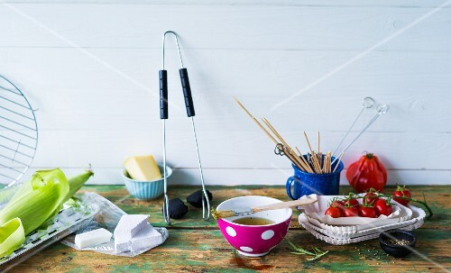 An arrangement of barbecuing utensils and ingredients
