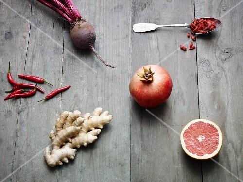 An arrangement of chillis, ginger, beetroot, pomegranate and grapefruit