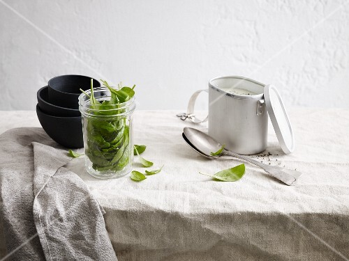 An arrangement of soup bowls, spinach leaves and an insulated container