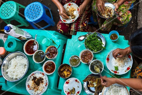 Burmese people eating street food at a market in Myanmar