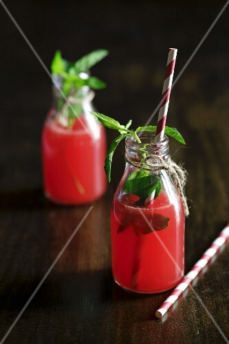 Two bottles of watermelon juice with fresh mint
