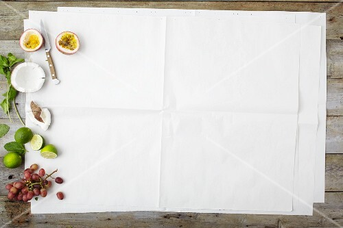 Fruit and coconut on one edge of a piece of white paper