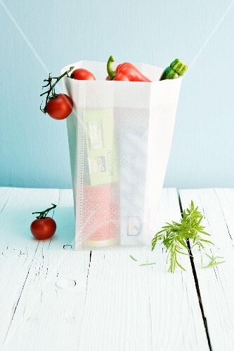 Fresh vegetables and convenience products in a shopping bag