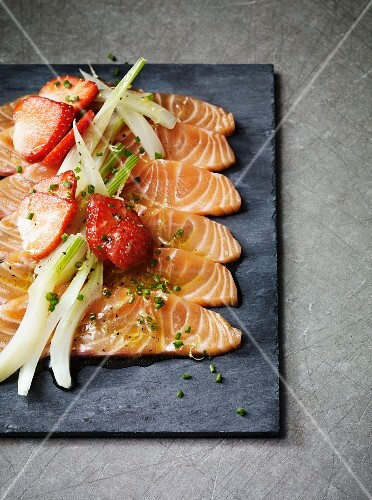 Salmon carpaccio with spring onions and strawberries