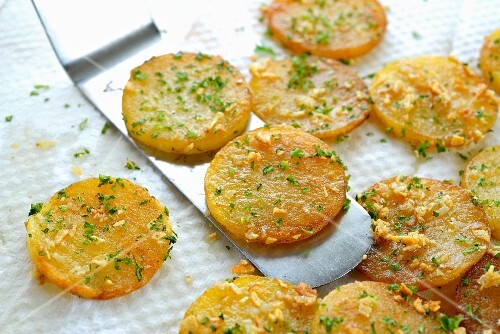 Sliced, fried potatoes with garlic and parsley