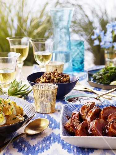 A table laid with pork fillet, egg salad and wine