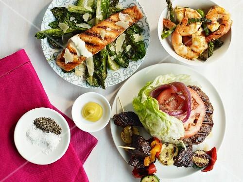 Various barbecue dishes: burger, salmon, prawns, kebabs, asparagus